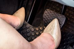 A woman`s foot on the brake pedal of car. A woman`s foot on the brake pedal of a car Royalty Free Stock Photo