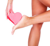 Woman`s foot and red heart Stock Photography