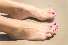 Woman's foots with a ring on a toe royalty free stock photography
