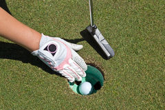 Woman's gloved hand, putter and golf ball in the cup Stock Image