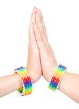 Woman& x27; s-händer med ett armband som mönstras som regnbågen, sjunker Isolerat på vit Arkivbild