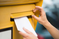 Woman& x27; s-händer som sätter in bokstaven i brevlåda royaltyfria bilder