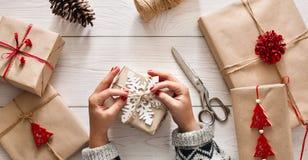 Woman& x27; s-händer som slår in jul, semestrar gåva med hantverket tvinnar Fotografering för Bildbyråer