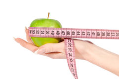 Woman's hand with apple and measure tape Stock Images
