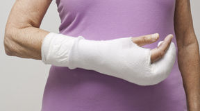 Woman's hand in bandage and cast. Senior woman's arm with bandages and cast over wrist and fingers following a fracture Stock Image