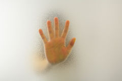 Woman's hand behind blurry glass Stock Photo