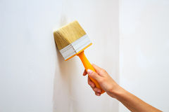 Woman's hand with a big brush paints the wall Royalty Free Stock Photography