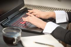Woman`s hand on a black-and-red laptop keyboard royalty free stock photos