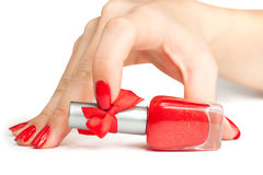 Woman's hand with a bottle of red nail polish Stock Photography