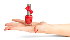Woman's hand with a bottle of red nail polish royalty free stock photo