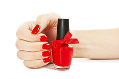Woman's hand with a bottle of red nail polish Royalty Free Stock Image