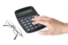 Woman's Hand on Calculator. A woman's hand rests on a calculator as she crunches some numbers Stock Images