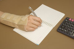 Woman's hand with carpal tunnel syndrome doing calculations. On sheet of paper Stock Photo