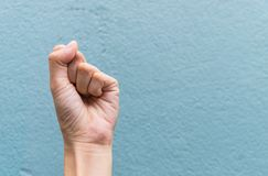 Woman`s hand with clenched fist. On blue background Stock Images