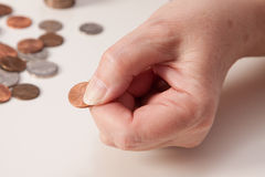 Woman's hand close up pinching a penny. With coins on the left on a white background Stock Photography