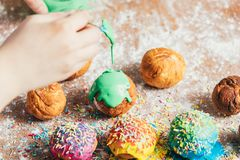 Woman`s hand coating a donut with green frosting. Homemade delicious foods Royalty Free Stock Image