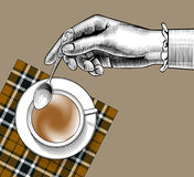 Woman`s hand with a coffee cup and spoon Stock Image