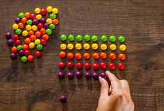Woman`s hand collects even row of colorful candies on a wooden. Background royalty free stock images
