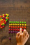 Woman`s hand collects even row of colorful candies on a wooden. Background royalty free stock photography