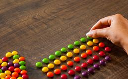 Woman`s hand collects even row of colorful candies on a wooden. Background royalty free stock photo