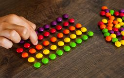 Woman`s hand collects even row of colorful candies on a wooden. Background stock image