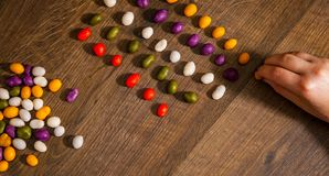 Woman`s hand collects even row of colorful candies on a wooden background. top view. With copy space Stock Photo