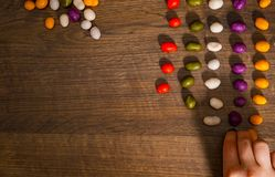 Woman`s hand collects even row of colorful candies on a wooden background. top view. With copy space Royalty Free Stock Images