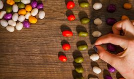 Woman`s hand collects even row of colorful candies on a wooden background. top view. With copy space Royalty Free Stock Image