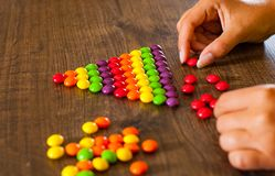 Woman`s hand collects even row of colorful candies on a wooden. Background royalty free stock photos