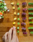 Woman`s hand collects even row of colorful Frozen mixed vegetables on a wooden background Royalty Free Stock Images