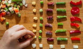 Woman`s hand collects even row of colorful Frozen mixed vegetables on a wooden background. Top view royalty free stock images