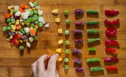 Woman`s hand collects even row of colorful Frozen mixed vegetables on a wooden background Royalty Free Stock Photography