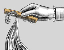 Woman`s hand combing hair with a retro comb. Vintage engraving stylized drawing. There is in addition a vector format EPS 8 Stock Photography