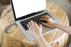 Woman's hand on computer notebook with eyeglasses on wooden desk. Woman's hand on laptop computer notebook with eyeglasses on wooden desk Royalty Free Stock Photo