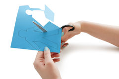 Woman's hand cutting a paper stick figure over white background Stock Images