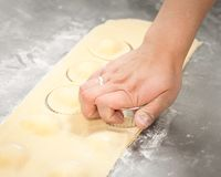 A woman`s hand cutting rolled out ravioli dough into circles. stock images