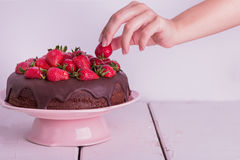 Woman's hand decorated with strawberry chocolate cake. Royalty Free Stock Image