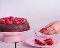 Woman's hand decorated with strawberry chocolate cake. Royalty Free Stock Images