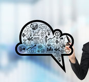 A woman's hand is drawing a cloud with business icons on the glass screen. Royalty Free Stock Images