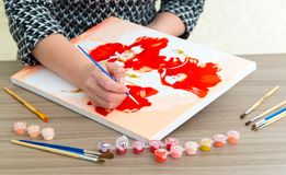Woman`s hand draws a painting with a brush and paints. A woman`s hand draws a painting with a brush and paints Stock Photography