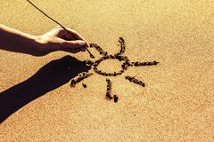 A woman`s hand draws the sun on the sand by the sea, close-up stock image