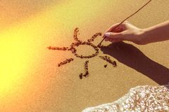 A woman`s hand draws the sun on the sand by the sea, the glow effect stock image
