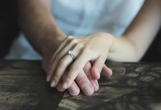 Woman`s hand with an engagement ring on man`s hand, date in cafe Royalty Free Stock Images