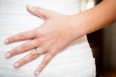 Woman's hand with engagement ring on wedding dress Royalty Free Stock Image