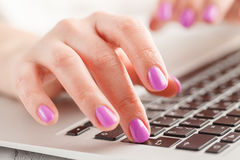 Woman`s hand entering data using laptop while holding a credit card in the other hand Stock Images