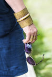 Woman's hand with eyeglasses and brass jewelry Royalty Free Stock Image