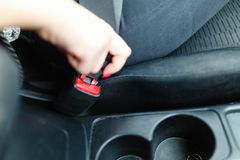 The woman& x27;s hand is fastened with a seat belt to start driving on the Car. royalty free stock photos