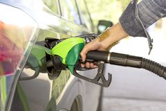 A woman`s hand filling up gas. For a new car stock image
