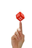 Woman's hand with a finger pointing and red dice. Woman`s hand with a finger pointing. On top of the finger is the red dice with the number six on each side. All Royalty Free Stock Photo