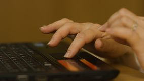A Woman`s hand with the fingers on a laptop mousepad. Woman`s hand using laptop mouse Royalty Free Stock Images